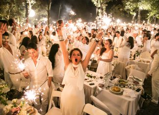 Guests in white hold up sparklers, express excitement.