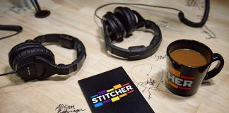 Coffee, headphones, and a stitcher sign on a wooden table covered in signatures.